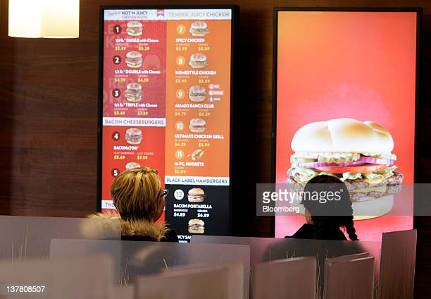 Customers review the video menu board at a Wendy's Co restaurant in Columbus Ohio US on Friday Jan 27 2012 Wendy's Co the thirdbiggest US fastfood...
