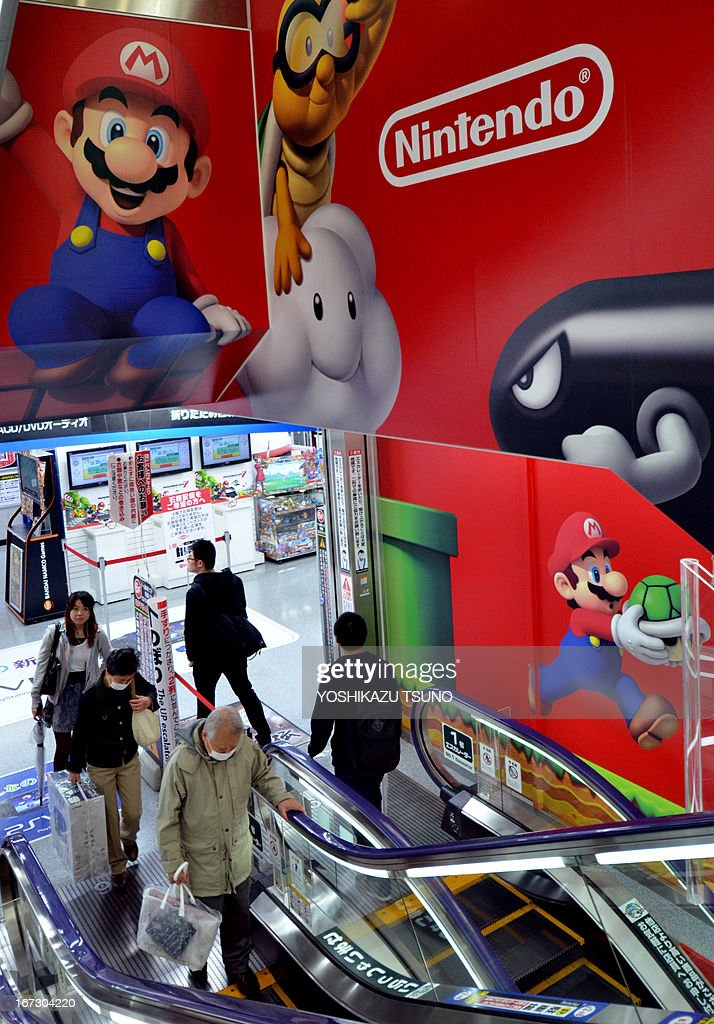 Customers ride an escalator past an advertisement for Japanese videogame giant Nintendo at an electrical shop in Tokyo on April 24, 2013. Japanese video game giant Nintendo on April 24 forecasted an eight-fold jump in net profit for the current fiscal year after saying it had returned to the black, helped by a weaker yen. AFP PHOTO / Yoshikazu TSUNO
