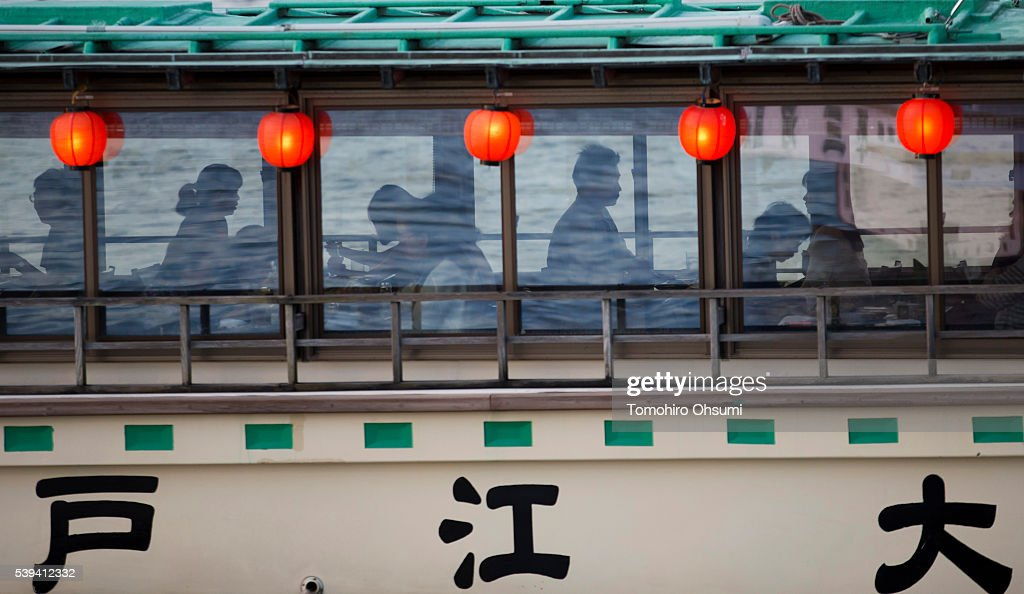 Customers ride on a yakatabune, or traditional low barge style boat as it sails through Tokyo Bay on June 11, 2016 in Tokyo, Japan. About 35 companies operate over 100 yakatabune boats in Tokyo offering services such as dinner or karaoke inside the boats while cruising in Tokyo's bay area, according to the Tokyo Yakatabune Association.