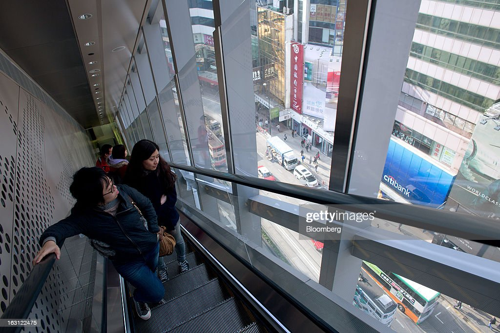 Customers ride on an escalator at Hysan Development Co.'s Hysan Place mall in the Causeway Bay district of Hong Kong, China, on Monday, March 4, 2013. Hysan is scheduled to release earnings on March 6. Photographer: Lam Yik Fei/Bloomberg via Getty Images