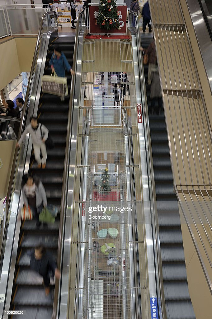 Customers ride on escalators in an Aeon Co. shopping center in Tokyo, Japan, on Friday, Nov. 9, 2012. Aeon Co. is Japan's largest supermarket operator. Photographer: Akio Kon/Bloomberg via Getty Images