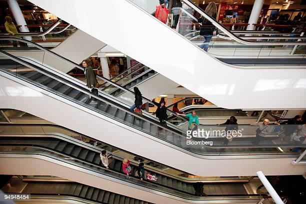 Customers ride the escalators at the Debenhams department store on Oxford Street in London UK on Monday May 18 2009 UK consumer spending slumped the...