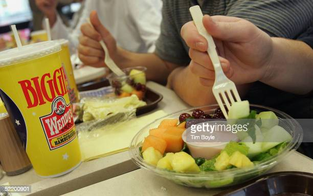 Customers sample a complimentary fruit cup and fruit bowl inside a Wendy's restaurant February 15 2005 in Glenview Illinois Wendy's introduced a new...