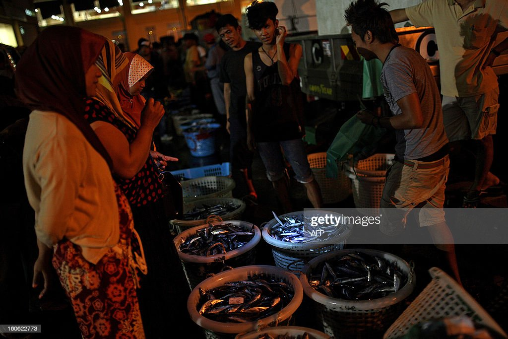 Customers (R) select fish from the fresh catch of the day at the Sandakan central fish market in the Malaysian Borneo state of Sabah on February 4, 2013. Sandakan is the second-largest city in Sabah, eastern Malaysia, on the northeastern coast of Borneo.