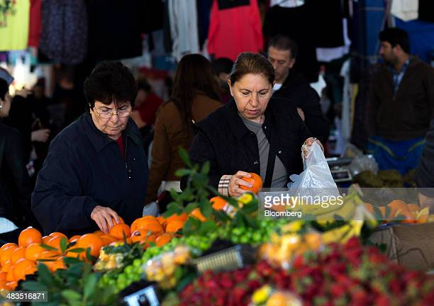 Customers select oranges for sale at a stall in the Yesilkoy street market in Istanbul Turkey on Wednesday April 9 2014 Turkish central bank Governor...