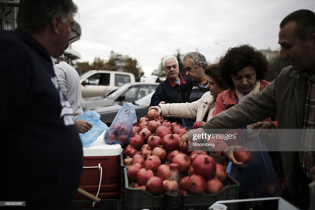 Customers select pomegranates from a stall at a farmers' market in Thessaloniki, Greece, on Saturday, Nov. 16, 2013. Greek Prime Minister Antonis Samaras, who survived a no-confidence vote on Nov. 11 with his parliamentary majority reduced to four, is trumpeting the first economic growth in seven years for 2014. Photographer: Konstantinos Tsakalidis/Bloomberg via Getty Images