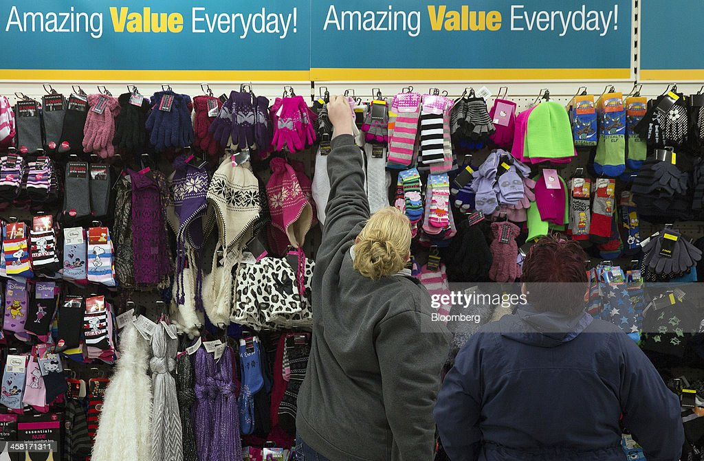A customers selects a pair of gloves from a display of winter clothes inside a Poundland discount store, operated by Poundland Holdings Ltd., in Birmingham, U.K., on Friday, Dec. 20, 2013. U.K. discount retailer Poundland has hired Rothschild to manage its IPO, according to the Sunday Times newspaper. Photographer: Simon Dawson/Bloomberg via Getty Images