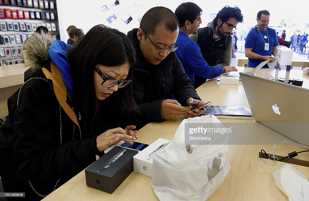 Customers set up new Apple Inc. iPhone 5 devices at a store in San Francisco, California, U.S., on Friday, Sept. 21, 2012. Apple Inc. is poised for a record iPhone 5 debut and may not be able to keep up with demand as customers lined up in Sydney, Tokyo, Paris and New York to pick up the latest model of its top-selling product. Photographer: David Paul Morris/Bloomberg via Getty Images