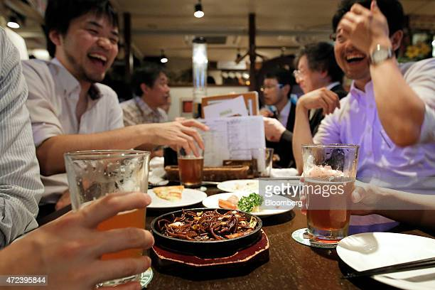 Customers share a laugh as they sit eating and drinking inside the Bakusyu Club Popeye bar in the Ryogoku neighborhood of Tokyo Japan on Friday May 1...