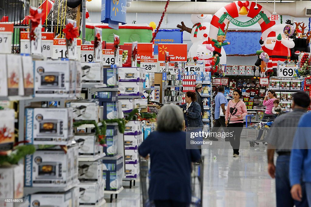 Customers shop at a Wal-Mart Stores Inc. location ahead of Black Friday in Los Angeles, California, U.S., on Tuesday, Nov. 26, 2013. Wal-Mart Stores Inc. said Doug McMillon, head of its international business, will replace Mike Duke as chief executive officer when he retires as the world's largest retailer struggles to ignite growth at home and abroad. Photographer: Patrick T. Fallon/Bloomberg via Getty Images