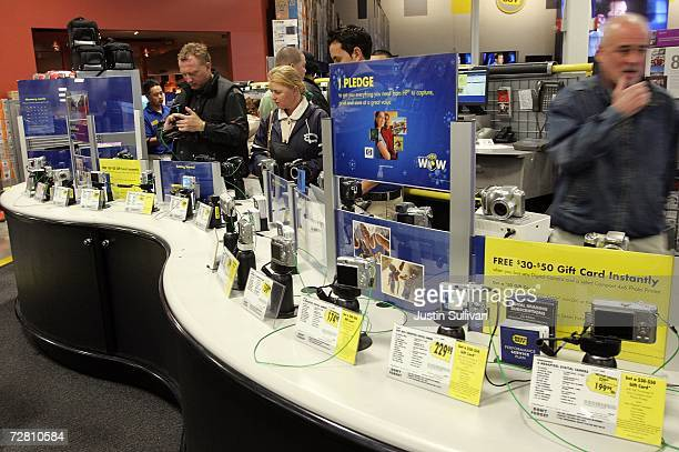 Customers shop for digital cameras at a Best Buy store December 12 2006 in San Francisco Best Buy Co reported that thirdquarter earnings rose 87...