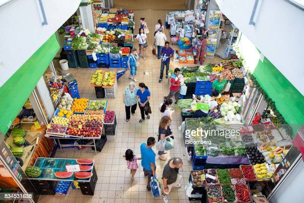 Customers shop for fruit and vegetable produce at an indoor market in Rome Italy on Thursday Aug 17 2017 Italy's economic recovery extended for a...