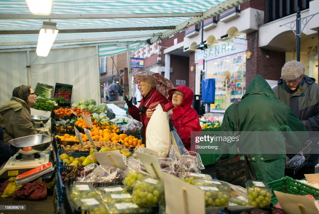 Customers shop for groceries at a fruit and vegetable stall at a market in Guildford, U.K., on Friday, Dec. 14, 2012. Standard & Poor's lowered its outlook on Britain's top credit rating to negative, citing weak economic growth and a worsening debt profile. Photographer: Simon Dawson/Bloomberg via Getty Images
