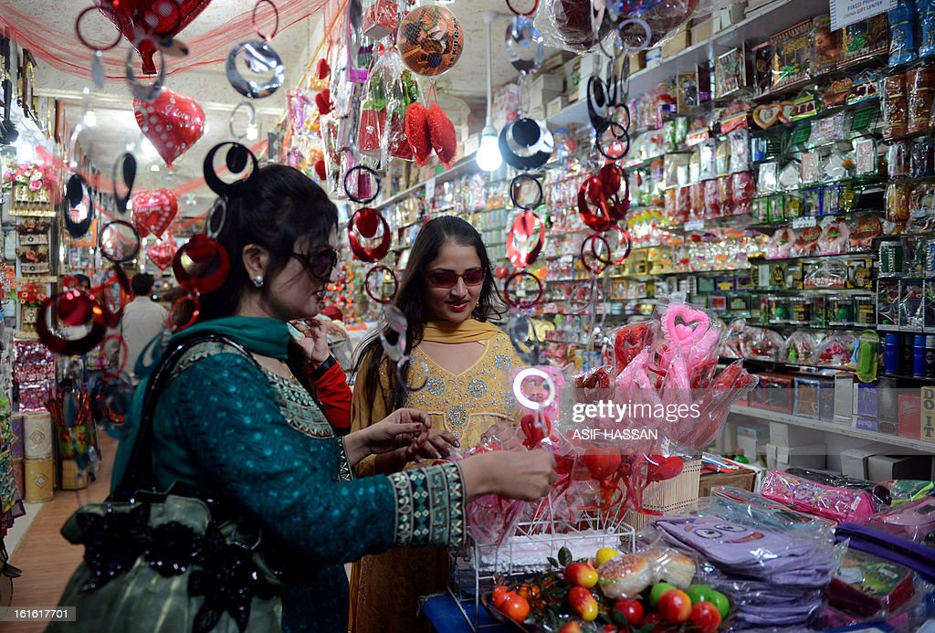 Customers shop for heart-shaped gifts ahead of Valentine's Day in Karachi on February 13, 2013. Valentine's Day is increasingly popular among younger Pakistanis, many of whom have taken up the custom of giving cards, chocolates and gifts to their sweethearts to celebrate the occasion. AFP PHOTO/Asif HASSAN