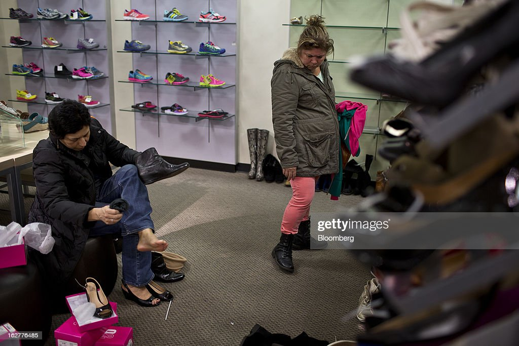 Customers shop for shoes at a J.C. Penney Co. store in the Queens borough of New York, U.S., on Tuesday, Feb. 26, 2013. Confidence among U.S. consumers jumped more than forecast in February as Americans adjusted to a higher payroll tax and signs of a recovering housing market spurred faith in the future. J.C. Penney Co. is scheduled to release earnings data on Feb. 27. Photographer: Victor J. Blue/Bloomberg via Getty Images