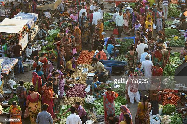 Customers shop for vegetables at a market in Ahmedabad on October 22 2013 The World Bank October 16 cut its growth forecast for India to 47 percent...