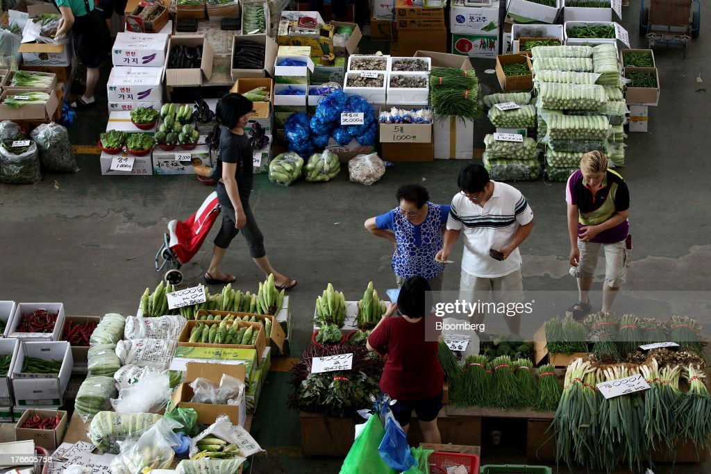 Customers shop for vegetables at Samsan Agricultural Wholesale Market in Incheon, South Korea, on Friday, Aug. 16, 2013. South Korean producer prices declined 0.9 percent in July from a year earlier after a 1.4 percent drop in June, the central bank said in a statement today. Photographer: SeongJoon Cho/Bloomberg via Getty Images