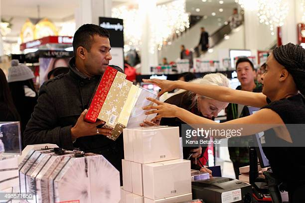 Customers shop in Macy's flagship store in Herald Square on Thanksgiving evening for early Black Friday sales on November 26 2015 in New York City...