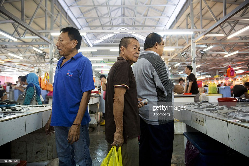 Customers shop inside the Chow Kit wet market in Kuala Lumpur, Malaysia, on Tuesday, July 22, 2014. Malaysian Airline System Bhd. (MAS), reeling from its second disaster in four months, plans to present a revival plan to its state-run parent Khazanah Nasional Bhd. this week, people familiar with the matter said, amid reports the national carrier is likely near the end of its days as a publicly traded company. Photographer: Brent Lewin/Bloomberg via Getty Images