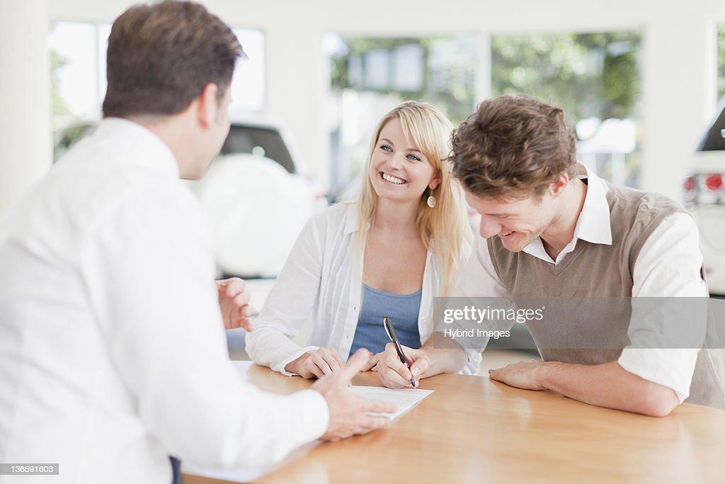 Customers signing at car dealership : Stock Photo