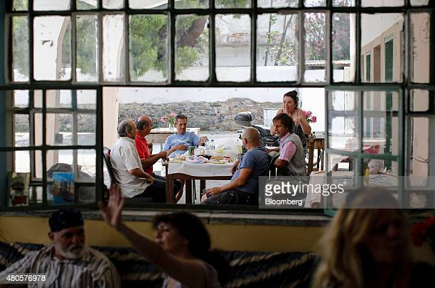 Customers sit and chat as they eat lunch outside an indoor market where an informal barter currency called TEM is used to exchange goods and services...