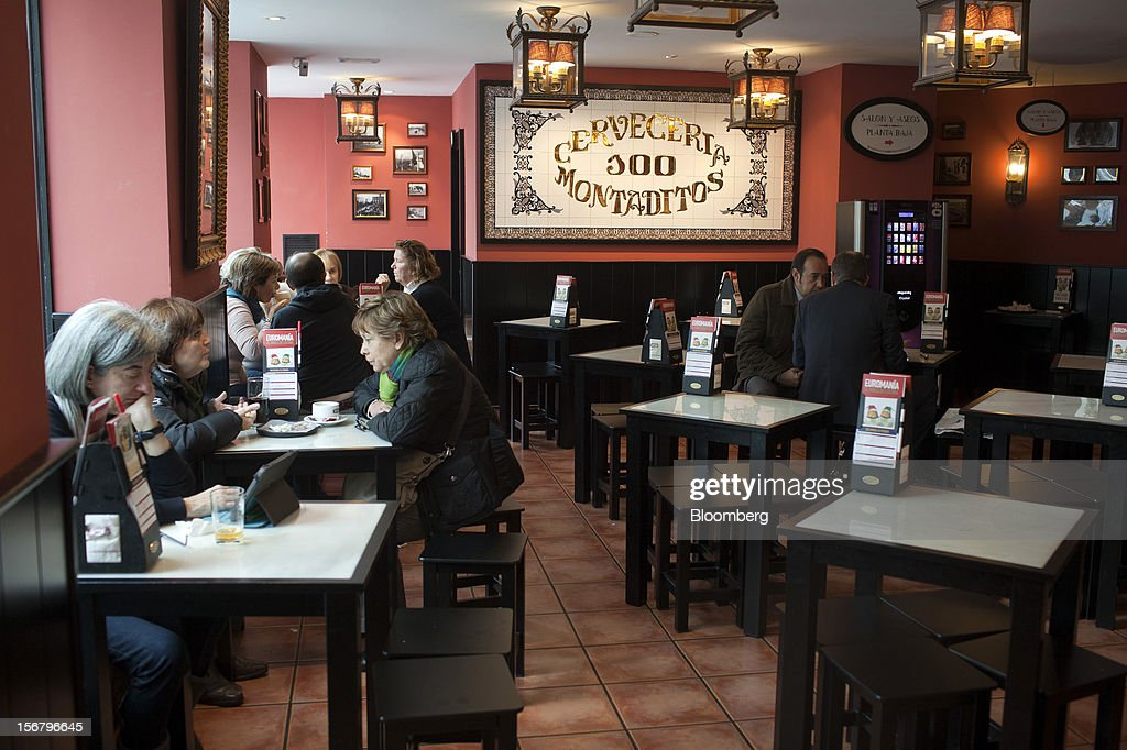Customers sit and dine at tables inside a 100 Montaditos restaurant in Madrid, Spain, on Wednesday, Nov. 21, 2012. The Madrid-based chain in January opened its first U.S. restaurant in Miami and aims to have eight outlets in Florida by next March. Photographer: Angel Navarrete/Bloomberg via Getty Images
