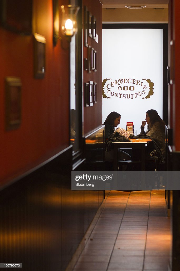 Customers sit and talk at a table in the window of a 100 Montaditos restaurant in Madrid, Spain, on Wednesday, Nov. 21, 2012. The Madrid-based chain in January opened its first U.S. restaurant in Miami and aims to have eight outlets in Florida by next March. Photographer: Angel Navarrete/Bloomberg via Getty Images