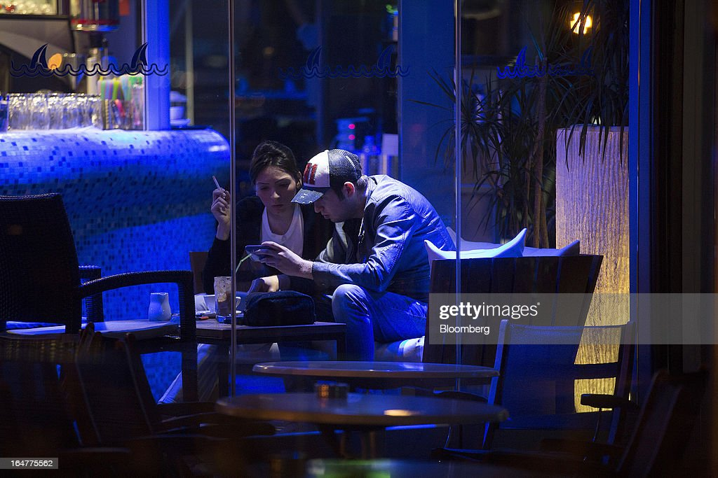 Customers sit and talk at a waterfront bar in Limassol, Cyprus, on Wednesday, March 27, 2013. The ECB said on March 25 it won't stop the Cypriot central bank from providing the island's banking sector with emergency funding. Photographer: Simon Dawson/Bloomberg via Getty Images