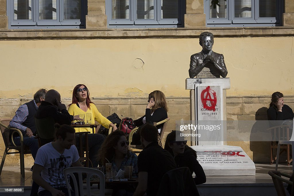 Customers sit and talk on a cafe terrace beside a monument marked with an anarchist logo in Nicosia, Cyprus, on Monday, March 25, 2013. In a replay of tensions over aid for Greece at the outset of the crisis, European governments had wrangled over aid for Cyprus for nine months, exposing holes in the revamped economic management system that was built in three years of emergency policymaking, often at all-night summits. Photographer: Photographer: Simon Dawson/Bloomberg via Getty Images