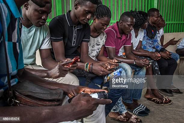 Customers sit and use their mobile phones while waiting to board a ferry boat in Abidjan Ivory Coast on Monday Aug 31 2015 The stability from the...