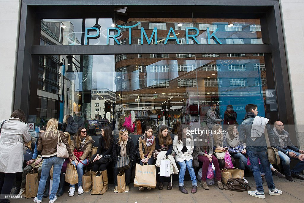 Customers sit and wait with their shopping bags on a window ledge outside a Primark store on Oxford Street in central London, U.K., on Monday, April 22, 2013. Associated British Foods Plc, the owner of the Primark discount-clothing chain, fell the most in three months after Credit Suisse Group AG said it's unlikely the chain's profit growth can continue at the first half's pace. Photographer: Jason Alden/Bloomberg via Getty Images
