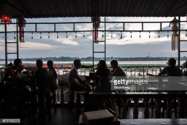 Customers sit at a bar with views of the Mekong river in Vientiane Laos on Thursday Nov 2 2017 Located in the Mekong region Southeast Asia's frontier...