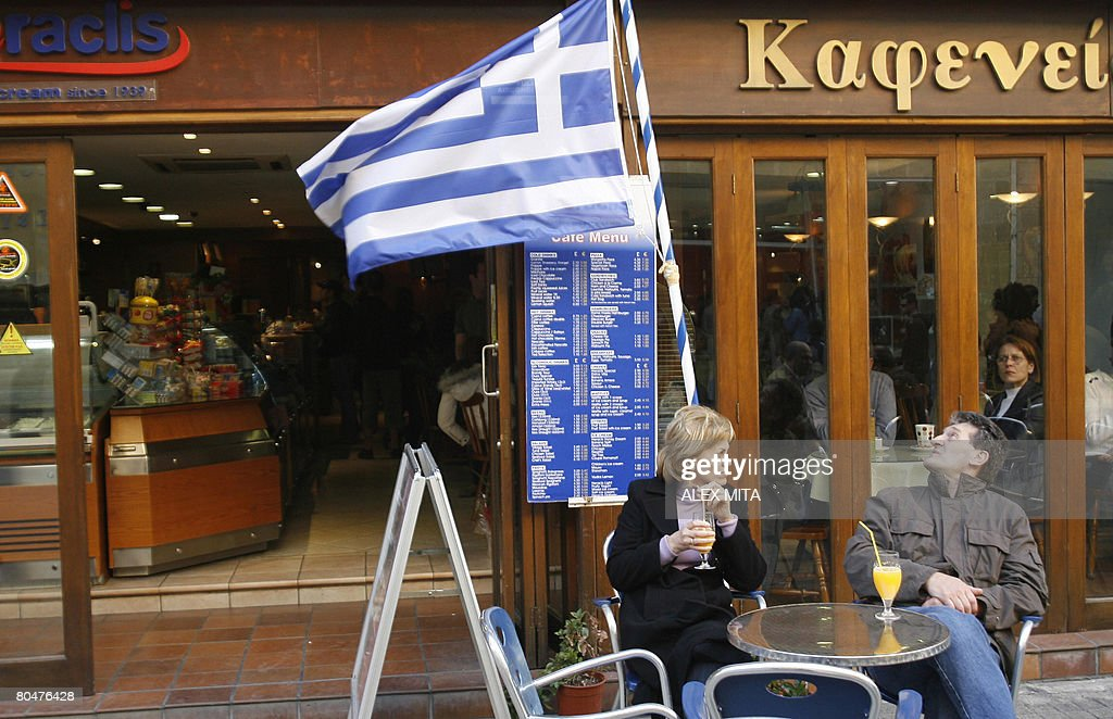 Customers sit at a cafe on the GreekCypriot side of the divided captial Nicosia's bustling Ledra street on April 1 2008 A symbolic crossing at Ledra...