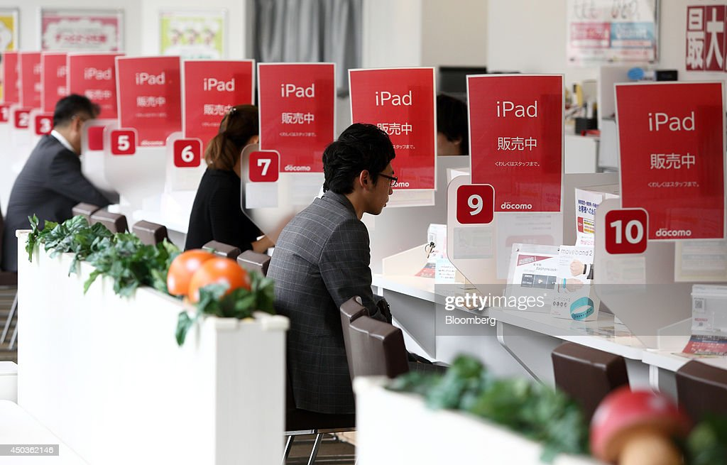 Customers sit at a service counter as signs advertising Apple Inc's iPads are displayed at an NTT Docomo Inc. store in Tokyo, Japan, on Tuesday, June 10, 2014. NTT Docomo, Japan's largest wireless carrier by subscribers, began offering Apple Inc's iPad today. Photographer: Tomohiro Ohsumi/Bloomberg via Getty Images