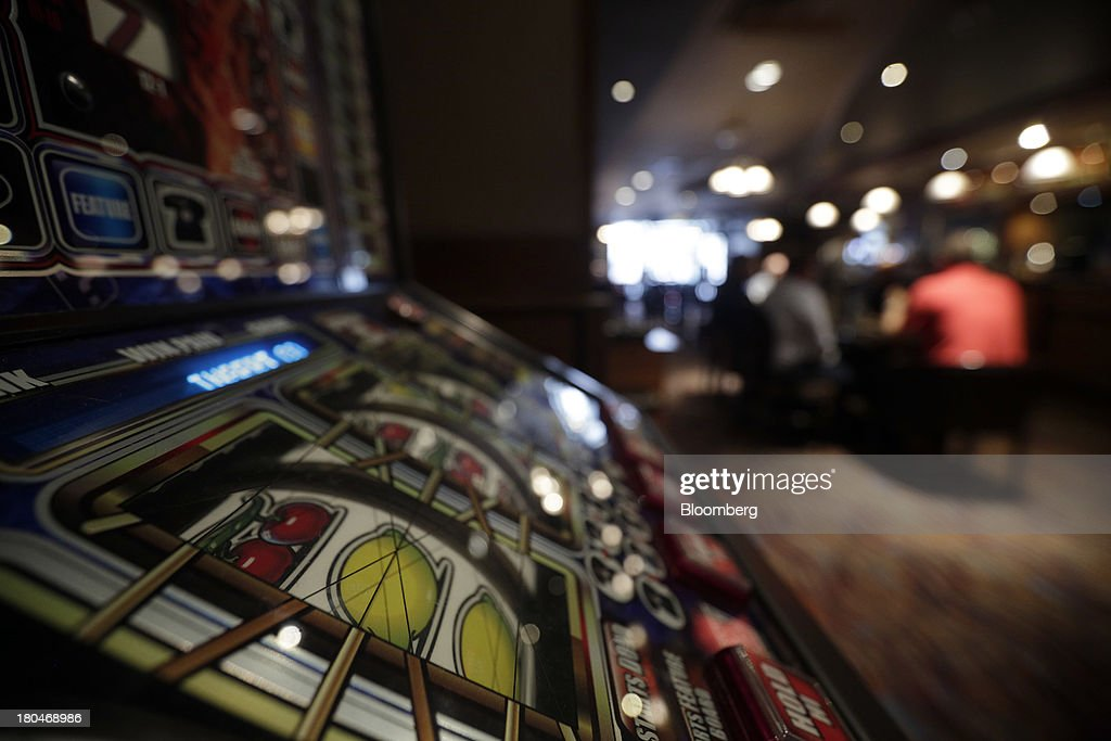 Customers sit at a table beyond a fruit coin slot machine inside a JD Wetherspoon Plc pub in London, U.K., on Friday, Sept. 13, 2013. JD Wetherspoon, who reported full year sales today, are planning to move into the Irish market next year, Chairman Tim Martin said in a recent interview. Photographer: Matthew Lloyd/Bloomberg via Getty Images