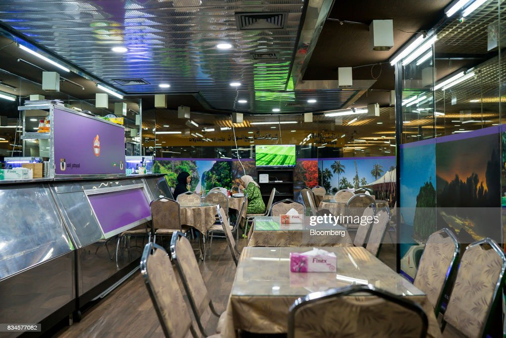 Customers sit at a table in an empty local Thai restaurant in Kuwait City, Kuwait, on Monday, Aug. 14, 2017. Kuwait will issue a tender to build the estimated $1.2 billion Dibdibah solar-power plant in the first quarter of 2018 as part of the countrys plans to produce 15 percent of power from renewable energy by 2030. Photographer: Tasneem Alsultan/Bloomberg via Getty Images