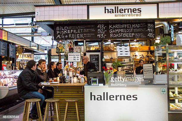 Customers sit at a traditional Danish 'open sandwich' café inside inside the TorvehallerrneKBH marketplace in Copenhagen Denmark on Sunday Jan 19...