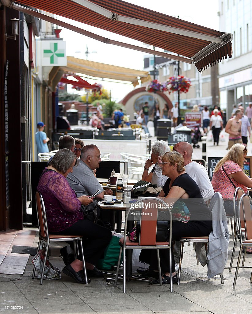Customers sit at an outdoor cafe terrace on the main shopping area of Hastings, U.K., on Tuesday, July 23, 2013. U.K. retail sales rose for a second month in June as discounts at department stores drove demand for clothes and electrical products. Photographer: Chris Ratcliffe/Bloomberg via Getty Images