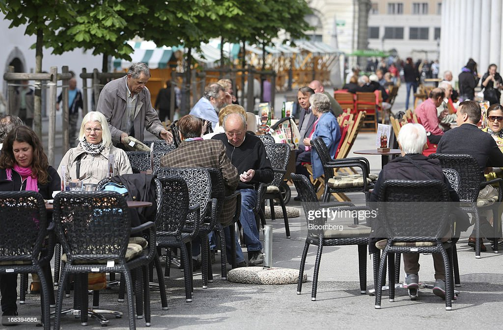 Customers sit at tables at an outdoor cafe terrace in Ljubljana, Slovenia, on Wednesday, May 8, 2013. Slovenia's recession will stretch into next year on weak domestic demand as the euro-area country teeters on the brink of needing an international bailout, the European Commission said. Photographer: Chris Ratcliffe/Bloomberg via Getty Images