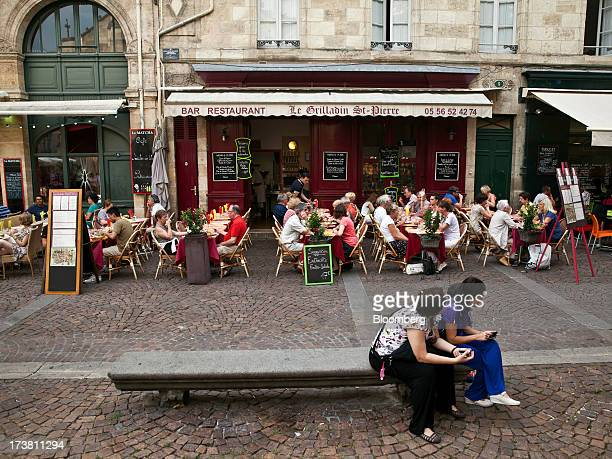 Customers sit at tables at an outdoor restaurant terrace in the St Pierre district of Bordeaux France on Wednesday July 17 2013 Austerity measures...