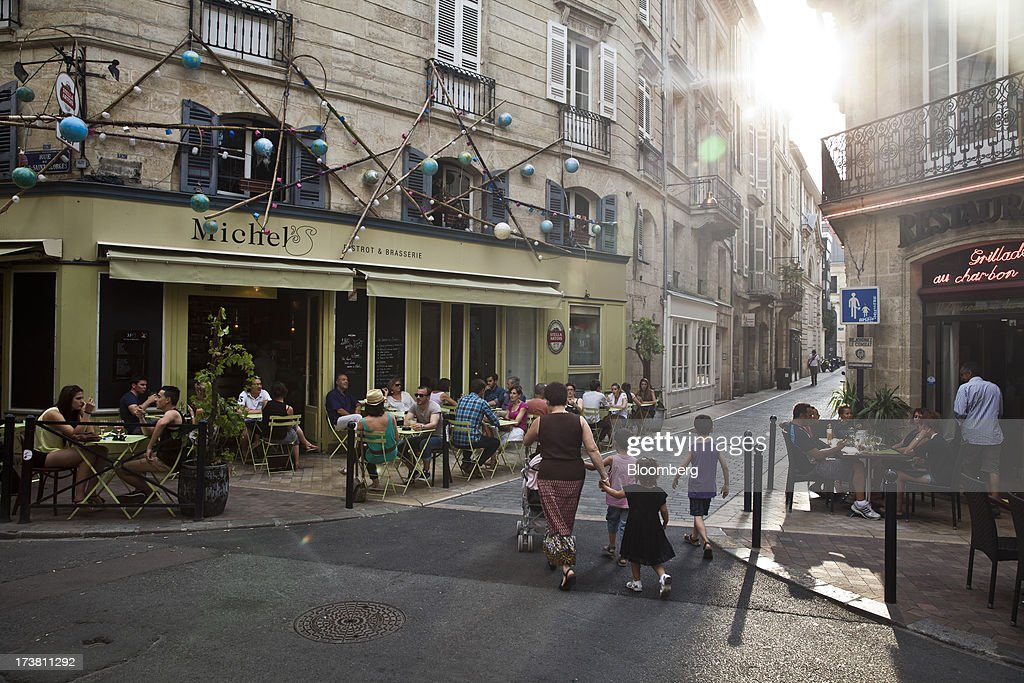 Customers sit at tables outside a restaurant in the St Pierre district of Bordeaux, France, on Wednesday, July 17, 2013. Austerity measures and rising unemployment are restraining consumer spending in Europe, while retailers including Groupe Auchan SA and Casino Guichard-Perrachon SA are competing more aggressively on price. Photographer: Balint Porneczi/Bloomberg via Getty Images