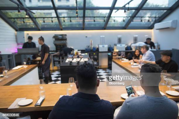 Customers sit at the chef's table inside the research and development kitchen at Gaggan restaurant in Bangkok Thailand on Friday May 5 2017 After his...