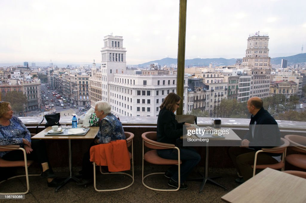 Customers sit beside windows onto the city skyline in the rooftop cafe at the El Corte Ingles department store in Barcelona, Spain, on Wednesday, Nov. 21, 2012. Bank of Spain Governor Luis Maria Linde said the government risks missing its budget targets this year and next, adding to doubts on Prime Minister Mariano Rajoy's ability to cut the deficit amid a five-year slump. Photographer: Stefano Buonamici/Bloomberg via Getty Images