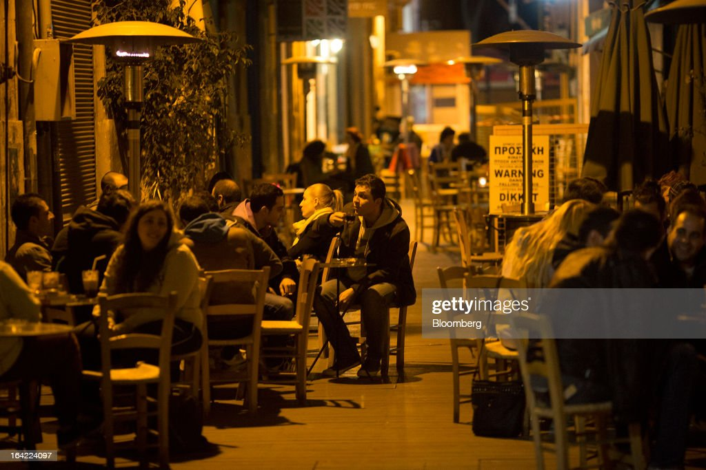 Customers sit in an outdoor restaurant during the evening in the old town of Nicosia, Cyprus, on Wednesday, March 20, 2013. European policy makers weighed how far to push Cyprus after lawmakers in the Mediterranean nation rejected an unprecedented levy on bank deposits, throwing into limbo a rescue package designed to keep it in the euro. Photographer: Simon Dawson/Bloomberg via Getty Images