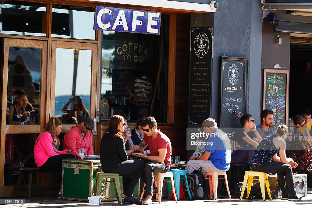 Customers sit in the outdoor area of a cafe in the Manly area of Sydney, Australia, on Sunday, May 19, 2013. The Reserve Bank of Australia cut its benchmark interest rate to a record low this month to boost businesses weakened by the currency's sustained strength, even as households reacted to earlier reductions. Photographer: Brendon Thorne/Bloomberg via Getty Images