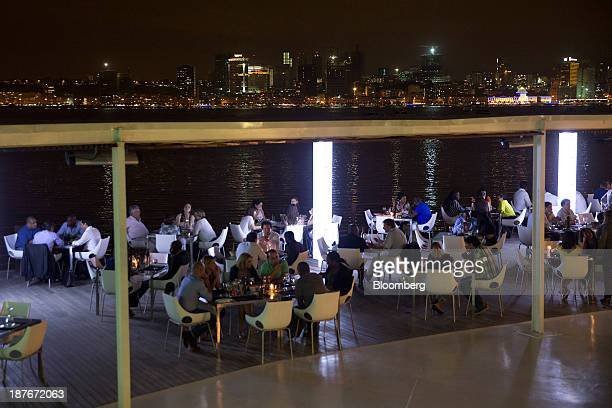 Customers sit on the terrace of the 'Cais de 4' luxury restaurant in Ilha district overlooking the city skyline in Luanda Angola on Thursday Nov 7...