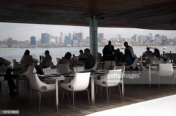 Customers sit on the terrace of the 'Cais de 4' luxury restaurant in Ilha district overlooking the city skyline illuminated at night in Luanda Angola...