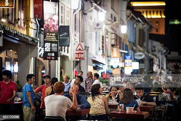 Customers sit outside at bar and restaurant tables along Club Street in the area of Chinatown in Singapore on Saturday Aug 23 2014 Singapore is...
