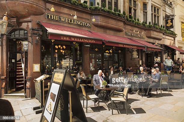 Customers sitting at sunny tables outside Wellington pub in the Strand