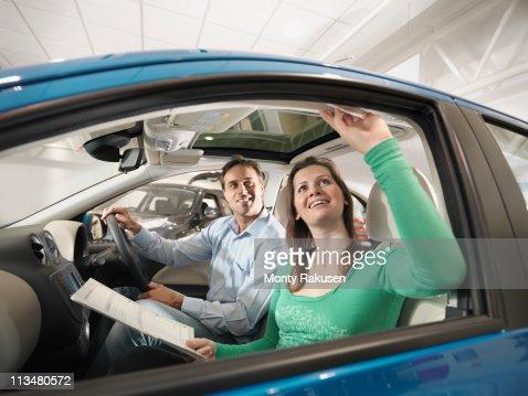Customers sitting in car look at car interior in car dealership